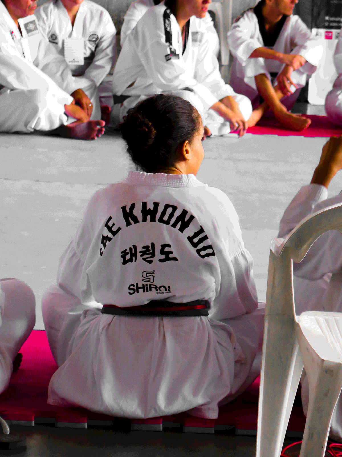 Taekwondo students sit listening to their instructor